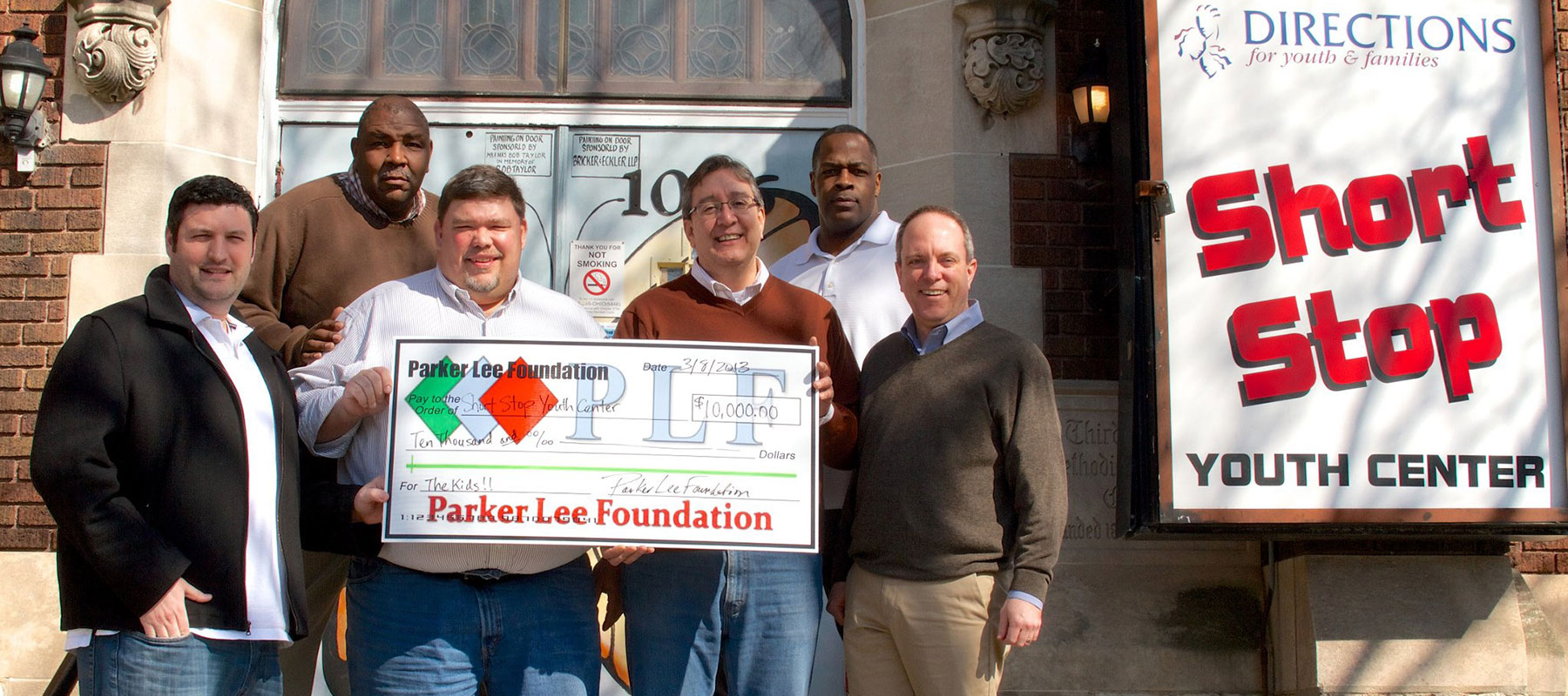 PLF crew holding check from the PBR 10K fundraiser