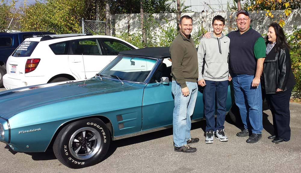 Group of people standing in front of a blue 1969 Ford Firebird