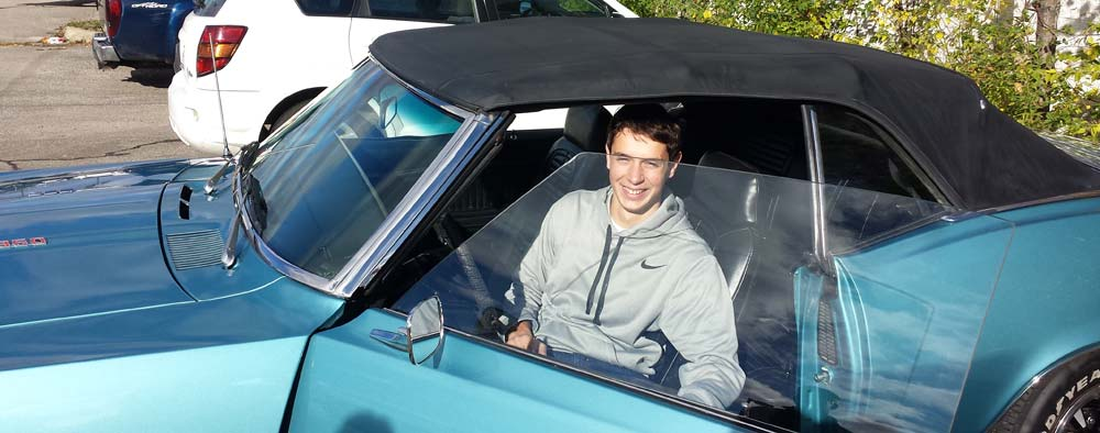 Teenager sitting in a blue 1969 Ford Firebird he just won in a raffle